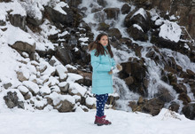 Little Girl In Winter Jacket On The Background Of The Winter Landscape, Mountain Waterfall