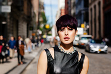 Close Up Portrait Of A Stylish Fashion Model With Short Purple Hair Standing In The Middle Of A Busy City Street