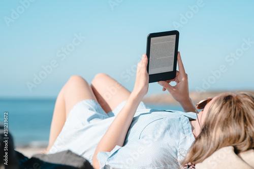 Frau liest mit E-Book Reader am Strand Canvas Print