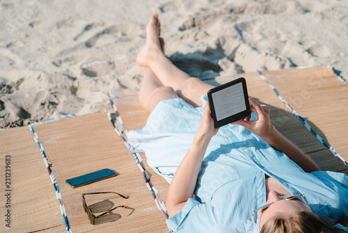 Canvas-taulu Frau liest mit E-Book Reader am Strand