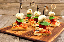 Caprese Pizza Skewers With Mozzarella, Basil, And Tomatoes. Appetizers Against A Rustic Wood Background.