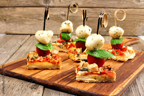 Fotobehang Voorgerecht Caprese pizza skewers with mozzarella, basil, and tomatoes. Appetizers against a rustic wood background.