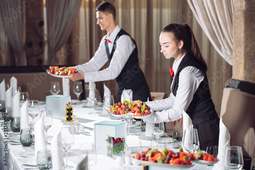 Canvas Print Waiters serving table in the restaurant preparing to receive guests