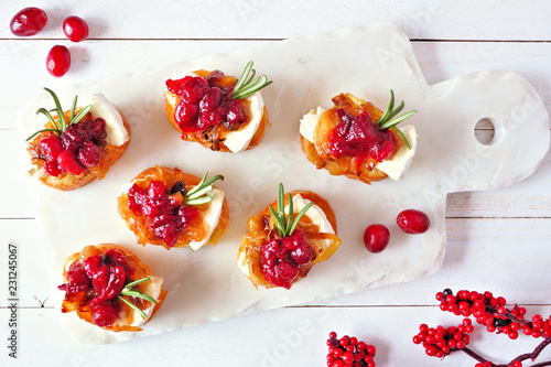 In de dag Voorgerecht Holiday crostini appetizers with cranberries, brie and caramelized onions. Above table scene on a white platter.
