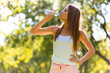 Fitness beautiful woman drinking water after exercising at the park