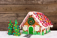 Sweet Christmas Gingerbread House With Candy Trees And A Rustic Wood Background