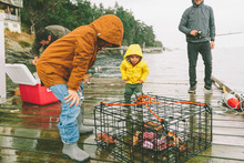 Fathers And Boys Crab Fishing Off Of A Dock In The Rain