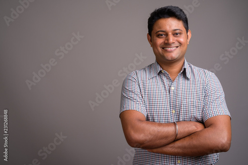 Photo  Portrait of young Indian businessman against gray background