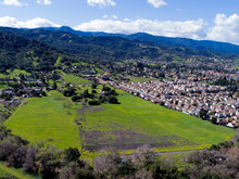 An Aerial Shot Of A Dense Neighborhood Of Two-story Homes Encroaching On Farmland, With Santa Cruz Mountains In The Background