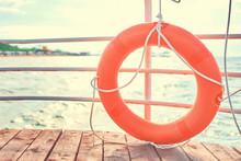 Orange Lifebuoy With Rope On Wooden Pier Near Sea.