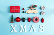 Set of Christmas decorations with word XMAS on blue background. Wooden toy car with Christmas tree on the roof, gift box and other baubles.