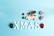 Christmas background with decorations and space for text on blue. Wooden toy car with Christmas tree on the roof and other baubles.