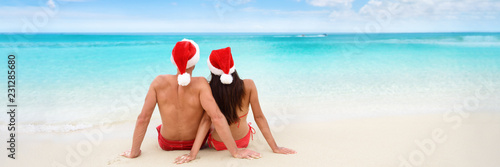 Photo  Christmas tropical sun vacation destination vacation holidays santa hat couple relaxing sitting on beach banner background for text advertisement for New Year holiday season