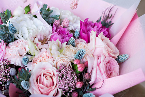 Beautiful bouquet in pink wrapping paper. Roses and other delicate beautiful flowers.