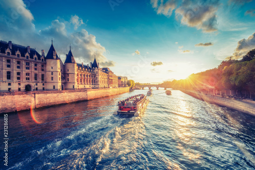 plakat Dramatic sunset over river Seine in Paris, France, with Conciergerie and Pont Neuf. Colourful travel background. Romantic cityscape.