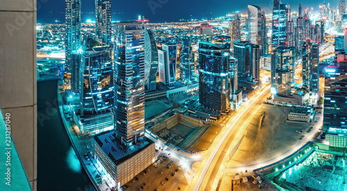 Spectacular urban skyline with colourful city illuminations. Aerial view on highways and skyscrapers of Dubai, United Arab Emirates.