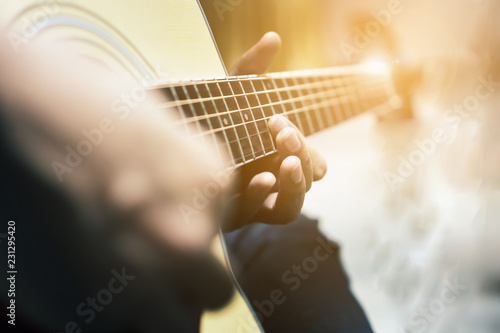 The man is playing guitar in the garden, Close-up male hand playing on acoustic guitar outdoor with bokeh and rays of sunlight Fototapet