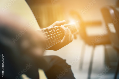 Fotografering  The man is playing guitar in the garden, Close-up male hand playing on acoustic guitar outdoor with bokeh and rays of sunlight