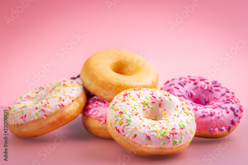 Heap of colorful donuts on pink background.