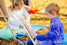 Cute Little Blond Child Boy In Blue Shirt Drawing Outdoor With Other Childern In Autumn Park. Creative Child Painting On Nature Sitting On Ground. Activity For Kids Concept.