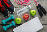 sneakers dumbbells bottle of water apple and measure tape
