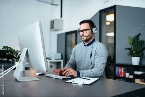 Young male customer support with headset working on the computer.