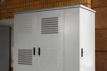 Outdoor Cabinet For Electrical Equipment On White Background. White Perforated Iron Cabinet On The Street.