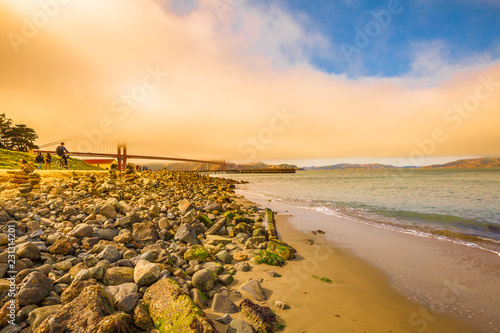 Tuinposter Amerikaanse Plekken Golden Gate Bridge with fog at sunset light from Crissy Field popular beach park for locals and tourists. Leisure and recreational activities concept. San Francisco in California, United States.