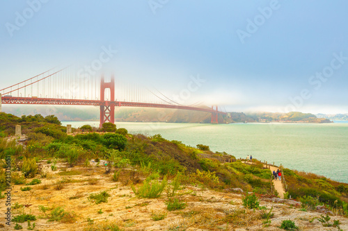Tuinposter Amerikaanse Plekken Red Golden Gate Bridge with green grass as foreground from south shore. Symbol of San Francisco, California, United States. American travel concept. Tourists and locals stroll around the bridge area.