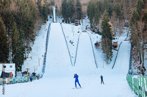 Extreme winter sports on the mountain. A ski jumper flying from a ski jumping hill tower. Harrachov, Czech Republic.