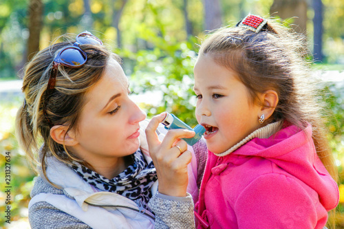 caring mom helps girl to use an inhaler against asthma Canvas Print