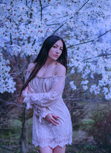 Pretty Attractive Lady With Dark Long Hair And Blue Eyes, Standing Near Blooming Magnolias, Dressing A Delightful Vintage Dress With Open Shoulders, Cool Artwork Photo Processing With Purple Color