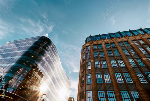 Foto  Modern offices and old middle of XX century buildings neighborhood with blue sky background
