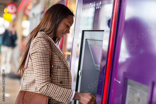 Fototapeta Young woman withdrawing cash from the ATM.