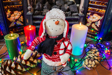 A Soft Toy Snowman Figure Sitting Beside The Fireplace.Plush Sitting Christmas Figurine