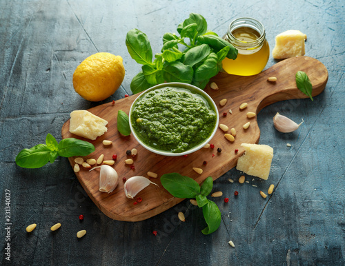 Fotografia Green Basil Pesto with parmesan cheese, pine nuts, garlic and lemon on wooden bo