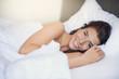 canvas print picture - Hübsche junge Frau liegt im Bett und lächelt