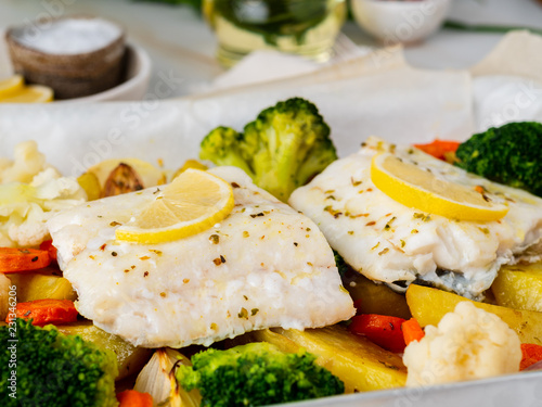 Fototapeta Fish cod baked with vegetables - healthy diet healthy food. Light white marble table, copy space, side view, close up obraz
