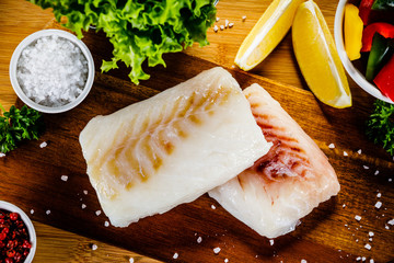 Fototapeta Fresh raw cod with herbs and vegetables served on cutting board on wooden table
