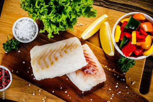 Fresh raw cod with herbs and vegetables served on cutting board on wooden table