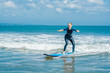 Joyful young woman beginner surfer with blue surf has fun on small sea waves. Active family lifestyle, people outdoor water sport lesson and swimming activity on surf camp summer vacation