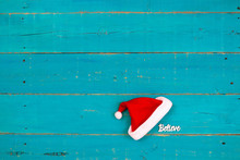 Blank Wood Sign With Red And White Christmas Santa Claus Hat And The Word Believe Hanging On Antique Rustic Teal Blue Wooden Sign; Holiday Background With Painted Copy Space
