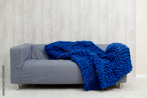 Blue merino wool blanket on grey sofa Wallpaper Mural