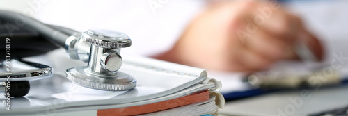 Cuadros en Lienzo Stethoscope head lying on medical forms closeup