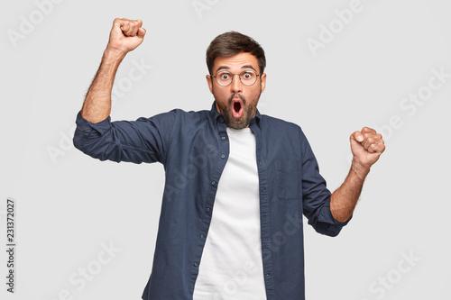 Cuadros en Lienzo Waist up shot of emotive Caucasian man has surprised facial expression, raises h