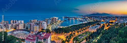 Night aerial panorama of Malaga, Spain with skyscrapers, streets, port, city hall and park during golden hour