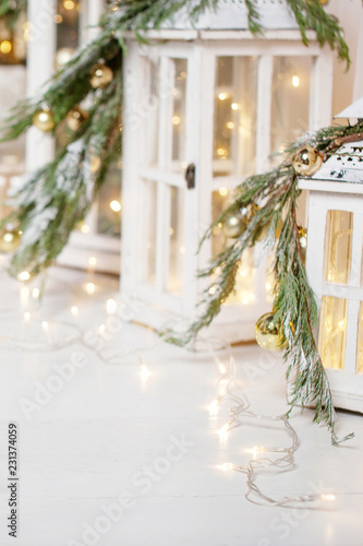 Photo  Christmas lanterns and snowy fir branches over white wooden background with lights