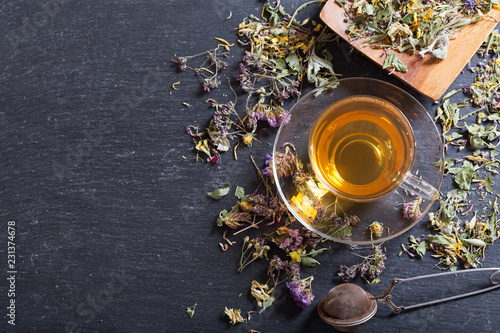 Cup of herbal tea with various herbs, top view