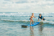 Father or instructor teaching his 4 year old son how to surf in the sea on vacation or holiday. Travel and sports with children concept. Surfing lesson for kids