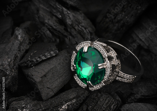 jewelry ring with big tourmaline gem on black coal background